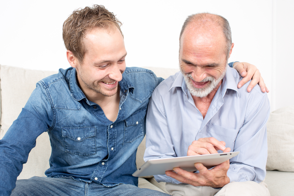 een zoon en vader die op de tablet kijken